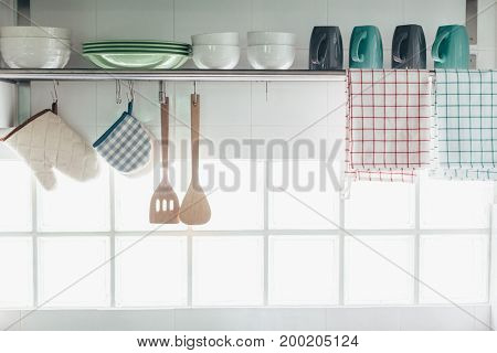 Home kitchen interior. Cooking utensils on a railing system and shelf with dishes above a window.