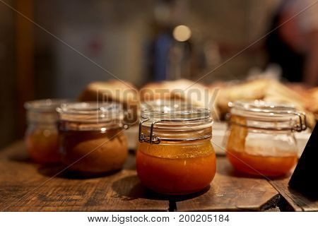 food, cooking and sale concept - craft jam or sauce at grocery store