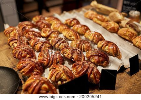 food, sale and baking concept - sweet buns with price tags at bakery store