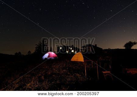 Night under the tent. People inside tent. Sky full of the stars. View on milky way.