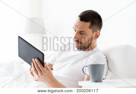 technology, internet, communication and people concept - young man with tablet pc computer in bed at home bedroom