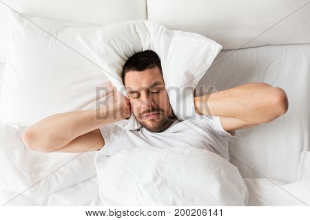 people, bedtime and rest concept - man lying in bed with pillow suffering from noise at home