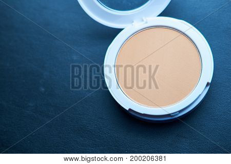 close up of foundation powder makeup isolated with black.