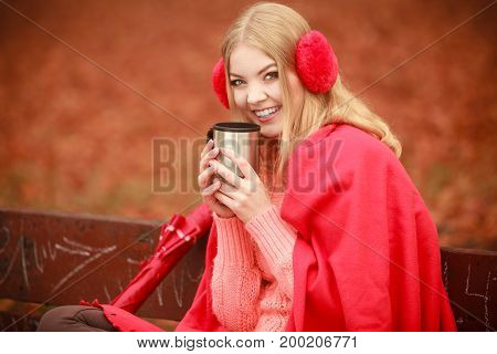 Happiness carefree and fall concept. Young happy woman relaxing in autumn park on bench enjoying hot drink holding mug with warm beverage. Orange leaves background