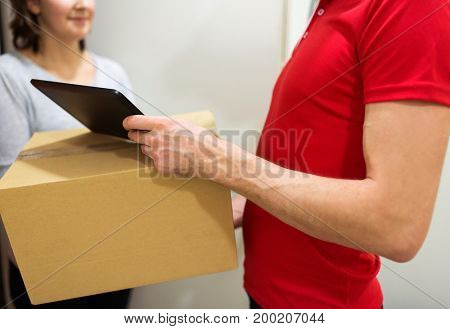 home delivery service, mail, people and shipping concept - man with tablet pc computer delivering parcel box to customer
