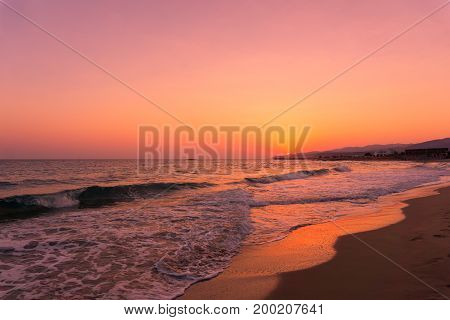 View on a Waves and a beautiful Sunrise at the Beach. Close-uo of a colorful Sunrise at a long Beach. A Beach in warm Light of a Sunrise. Natural Background.