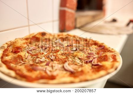 food, italian kitchen, culinary and cooking concept - baked pizza at pizzeria