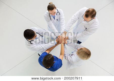 medicine, healthcare, teamwork and people concept - group of happy doctors holding hands together at hospital