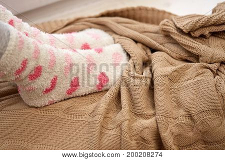 winter, comfort and people concept - woman or girl feet in socks and knitted plaid