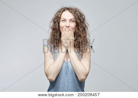 Portrait of amazed surprised young beautiful curly-haired female wearing grey t-shirt having astonished face expression,covering open mouth with both hands,looking at camera in shock & full disbelief