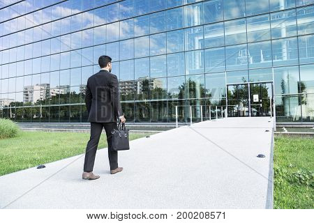 Anonymous businessman or worker in black suit with leather handbag or laptop case in his hand goes to work on the road to the entrance of a glass office building.