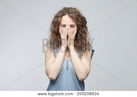 Disappointed dejected female with hair bun wearing blue loose T-shirt covering her face with hands being tired and exhausted. Desperate woman having depression hiding her crying face with hands.