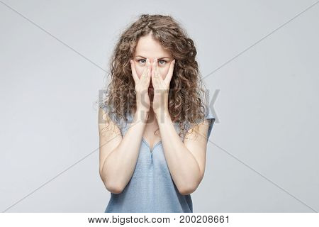 Worried young Caucasian lady with curly hair covering face with both hands feeling stressed out looking at camera through fingers with big blue eyes. Isolated shot on grey background.
