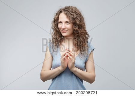 Portrait of attractive lady looking cunning and mysteriously at the camera holding hans together having some ideas in her mind. Curly-haired female with blue eyes concieving something with playful look.