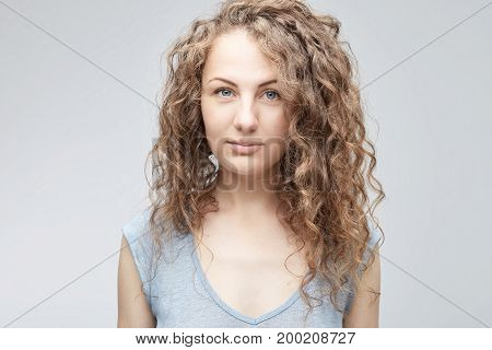 Close up shot of tender and cute teenage female with big blue eyes long curly hair and clean heathy skin looking straight at the camera while posing indoors against white studio wall.