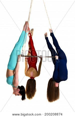 Young woman`s trio doing some acrobatic tricks on aerial luster