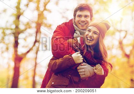 love, relationships, season and people concept - happy young couple hugging and laughing in autumn park