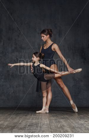 Young ballerina posing with the ballet teacher in studio