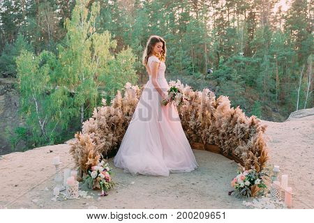 Bride With Rustic Bridal Bouquet Stands On The Rock. Wedding Ceremony, Decoration