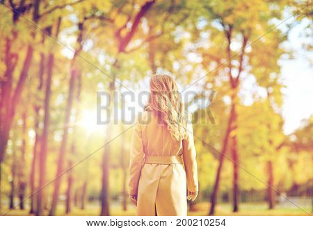 season and people concept - beautiful young woman walking in autumn park