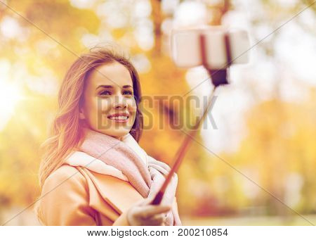 season, technology and people concept - beautiful young happy woman taking picture with smartphone selfie stick in autumn park