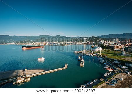 Batumi, Adjara, Georgia - May 25, 2016: Aerial View Of Port Dock On Sunny Evening At Sunset Or Sunrise Time. Sunny Landscape Of Local Embankment With Small Pleasure Boat On Large Tanker On Background.