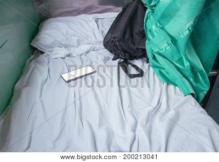 bag fabric black and cell phone on white bed in Interior train with copy space add text
