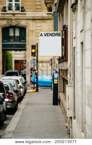 For sale a vendre signage on the corner of a building in Paris France with cars parked nearby