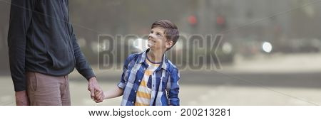 Digital composite of Father and son holding hands against blurry street