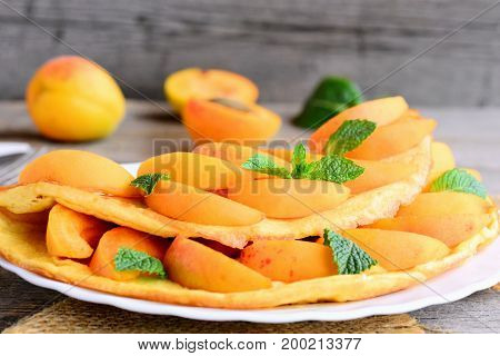 Homemade omelette or omelet stuffed with fresh apricot slices and mint on a white serving plate. How to make an omelette with filling. Summer delicious breakfast for the whole family. Closeup