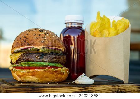 Close up delicious burger and potato wedges and plastic bottle of red juice on wooden board in restaurant