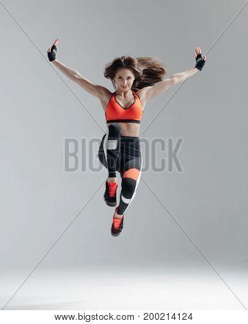 Young beautiful fitness female posing in studio