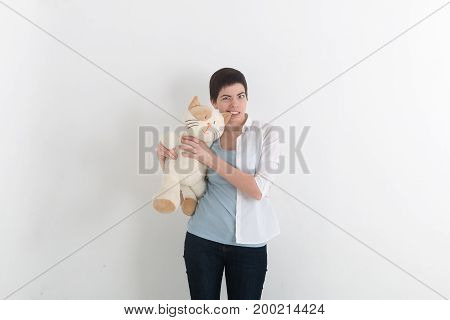 Furious woman bite her plush toy cat for ear gray studio background. Funny situation.