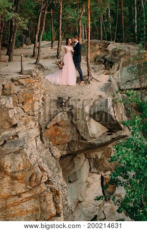 Newlyweds Standing At The Edge Of The Rock And Couple Looking Each Other With Tenderness And Love. B