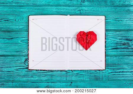 Heart of origami of red paper. Open notebook with clean pages and a paper heart. Red heart and diary on a blue background. Copy space