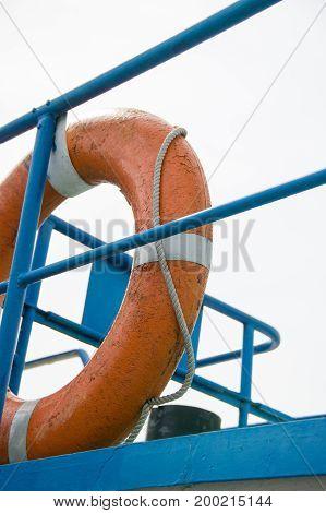 Orange life ring hanging on ship deck