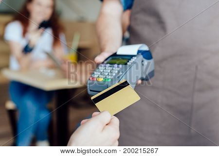 close-up partial view of person client holding credit card and waiter holding payment terminal