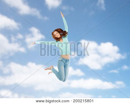 happiness, freedom, motion and people concept - smiling young woman jumping in air over blue sky background