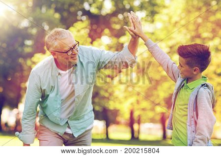 family, generation, gesture and people concept - happy grandfather and grandson making high five at summer park