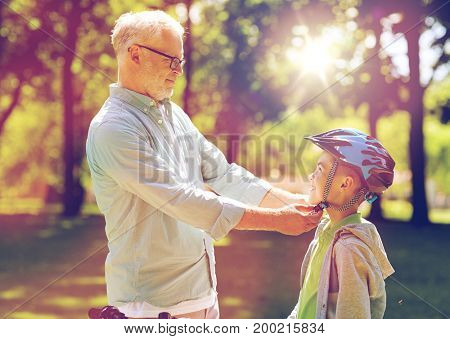 family, generation, safety and people concept - happy grandfather helping boy with bike helmet at summer park