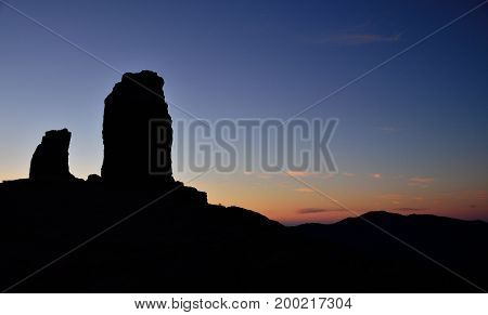 Roque Nublo backlit and the frog with vivid blue sky at sunset, Gran canaria, Canary islands