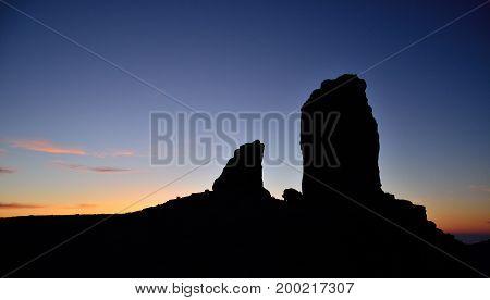 Roque Nublo and the frog backlit with intense blue sky at sunset, Gran canaria island
