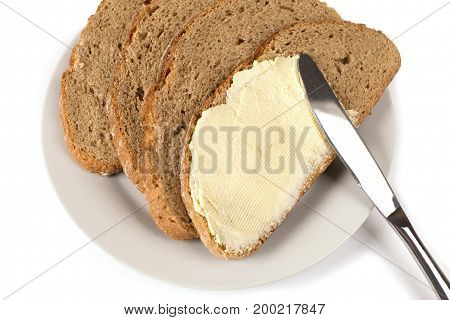 A knife spreading butter on bread on white