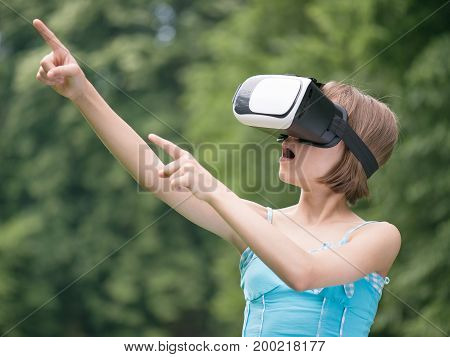Playful little girl using virtual reality goggles outdoor in summer park. Kid looking in VR glasses. Child have fun experiencing 3D gadget technology.