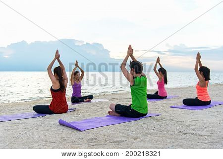 Asia people group making warrior pose on beach fitness sport yoga and healthy lifestyle. Healthy Concept