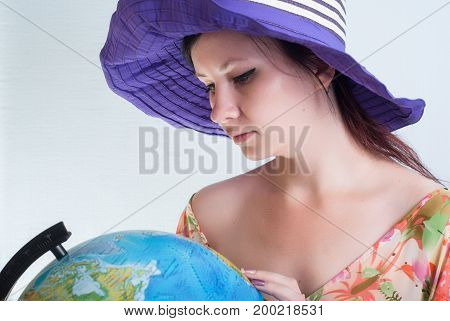 A Lovely Woman In A Hat Looking At A Globe.