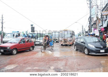 Dhaka, bangladesh, august 2017- The local roal is broken by heady shower and rain fall creating trafiic jam and obstacle for people to walk at Dhaka city in Bangladesh taken on August 17, 2017.