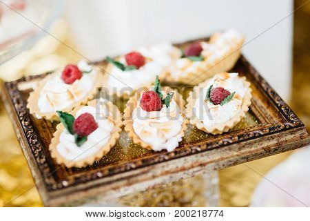 Delicious wedding reception candy bar Dessert table for a wedding party. Cakes with blackberries, raspberries and chocolate