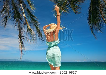 Happy woman in summer dress joyful jumping a background the blue sky and tropical beach. Sea landscape travel to Asia happiness emotion summer holiday concept.