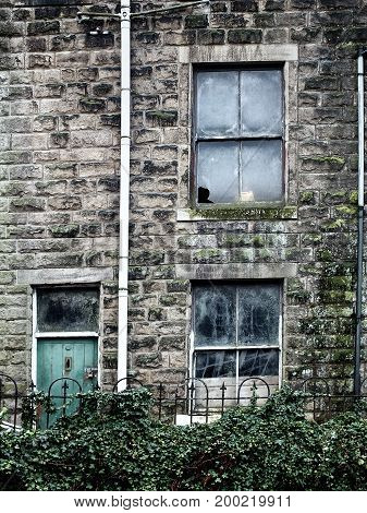 derelict abandoned house with broken windows and ivy growing up the walls with a green wooden door and stone walls in england